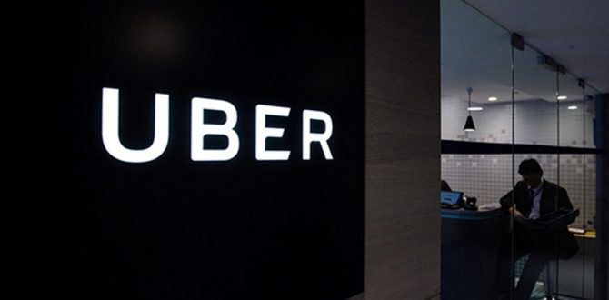 Uber signage is seen as an employee sits in the entrance of the ride hailing giants office in Hong Kong 670x330 - Uber Takes on Commuting With Express Car Pool Service